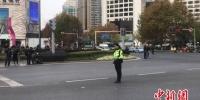 一位交警站在马路中央默哀,悼念大屠杀遇难者。 杨颜慈 摄 - 江苏新闻网