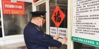 图为工作人员张贴宣传标语。 江苏省市场监管局供图  - 江苏新闻网