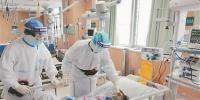 江苏省人民医院呼吸与危重症医学科副主任、主任医师,武汉市第一医院国家医疗队联合专家组组长齐栩(右一)和同事在武汉市第一医院重症监护病区给危重症患者进行检查。 - 新浪江苏