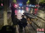 30日晚,南通市公安局崇川分局学田所民警救助被大风摔倒摔伤的群众。 警方供图 - 江苏新闻网